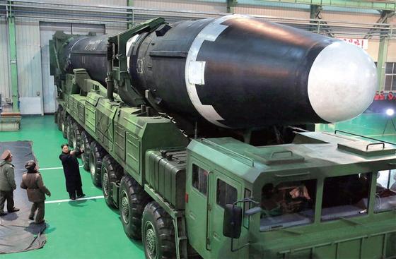 김정은 북한 노동당 위원장(왼쪽 아래)이 이동식발사대(TEL)에 실린 대륙간탄도미사일 (ICBM)급 화성-15형을 살펴보고 있다. [노동신문]