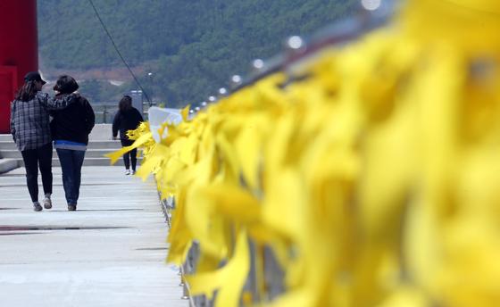 2014년 4월 전남 진도 팽목항에서 세월호 실종자 가족이 무사귀환을 바라는 노란 손수건들을 보며 걷고 있다. [중앙포토]