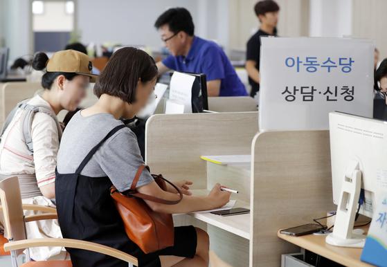 지난해 6월 서울 송파구의 한 주민센터에서 보호자들이 아동수당을 신청하고 있다. [연합뉴스]