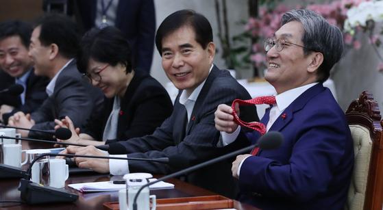 노영민 비서실장이 14일 청와대에서 열린 수석보좌관회의에서 '노타이'로 참석해도 된다고 하자 웃으며 넥타이를 풀고 있다. 청와대사진기자단