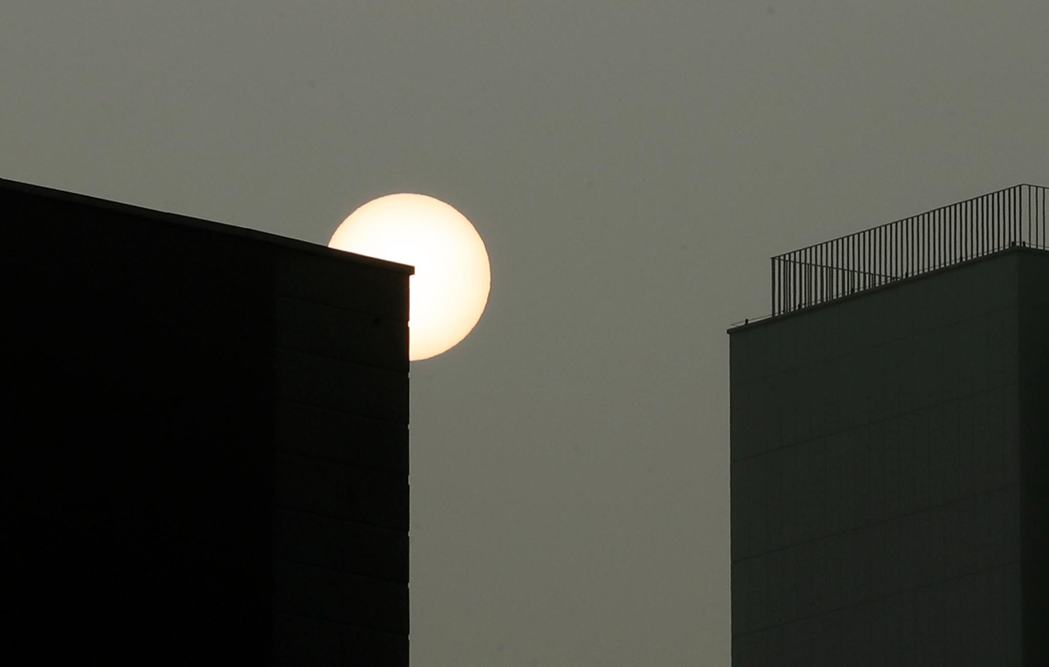 14일 미세먼지가 전국적으로 기승을 부리고 있는 가운데 수도권에 연이틀 비상저감조치가 내려졌다. 이날 오전 서울 도심 빌딩 사이로 솟은 해가 미세먼지 탓에 달처럼 보인다. 변선구 기자