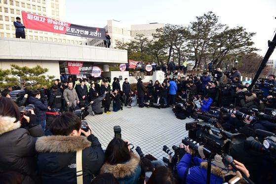 양승태 전 대법원장이 지난 11일 대법원 청사 앞에서 입장 발표를 하고 있는 가운데 법원 노조원들이 정문 구조물에 올라가 구속 수사를 요구하는 시위를 벌이고 있다. [오종택 기자]
