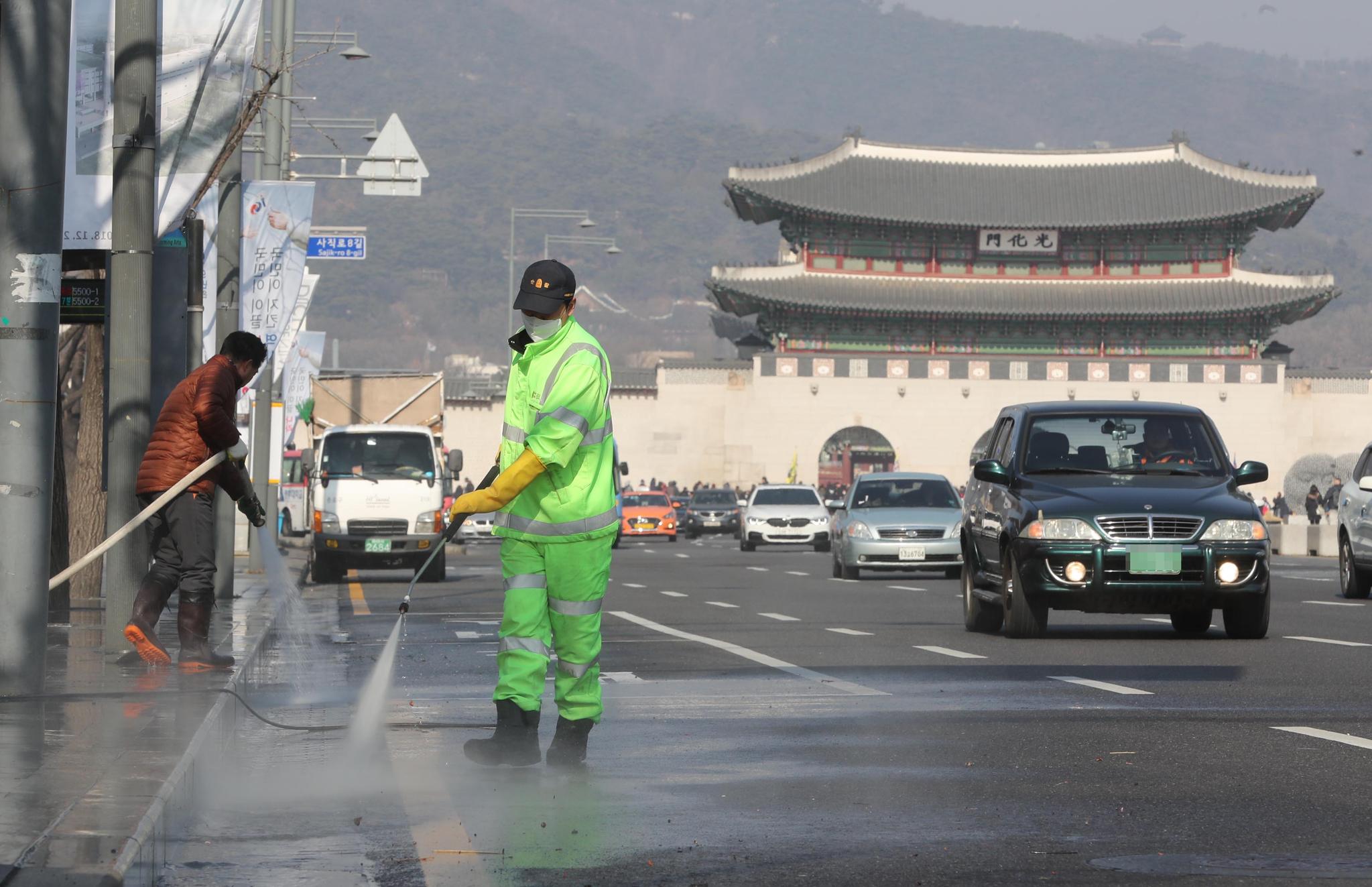 수도권에 미세먼지 비상저감 조치가 발령된 13일 오후 서울 종로구청 관계자들이 미세먼지를 줄이기 위해 세종문화회관 앞 도로에 물을 뿌리고 있다. 강정현 기자