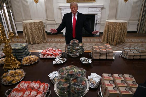 트럼프 미국 대통령이 14일(현지시간) 백악관에서 대학 풋볼 우승팀을 초청해 패스트푸드 파티를 주재하고 있다. [AP=연합뉴스]