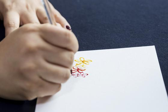 캘리그래피를 쓸 수채화 종이에 글씨와 어울리는 꽃을 그리는 작업을 하고 있다.