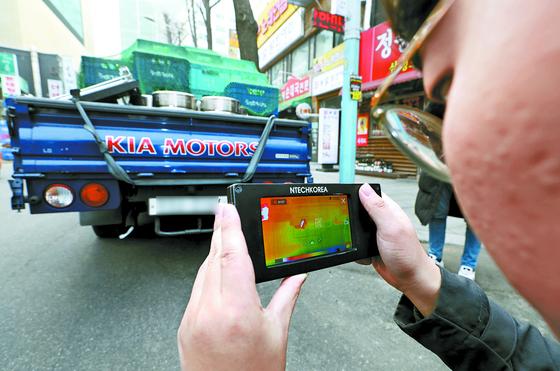 서울시 차량공해저감과 관계자들이 14일 광화문 인근에서 배출가스 단속 활동을 하고 있다. [뉴시스]