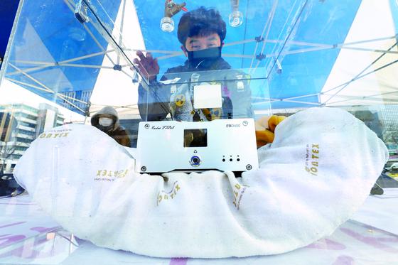 지난해 11월 서울 광화문에서 시민단체 활동가가 메모리폼 베개에서 라돈 발생 수치를 측정하는 장면. [뉴스1]
