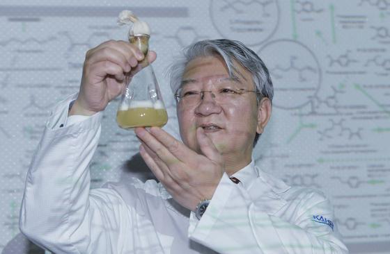 이상엽 KAIST 교수가 14일 KAIST 연구실에서 대장균으로 만든 휘발유가 든 실험도구를 들고 있다. 15일 네이처 카탈리시스에 실린 바이오 기반 화학물질 합성지도가 이 교수의 뒤에 있다. 이 교수는 시스템 대사공학을 이용해 바이오매스에서 화학물질을 생산하는 세계적 전문가다. 프리랜스 김성태
