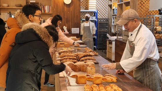지난 5일 서울 한남동 오월의 종 매장에서 정웅 대표가 매장을 찾은 고객들에게 빵에 대해 설명하고 있다.