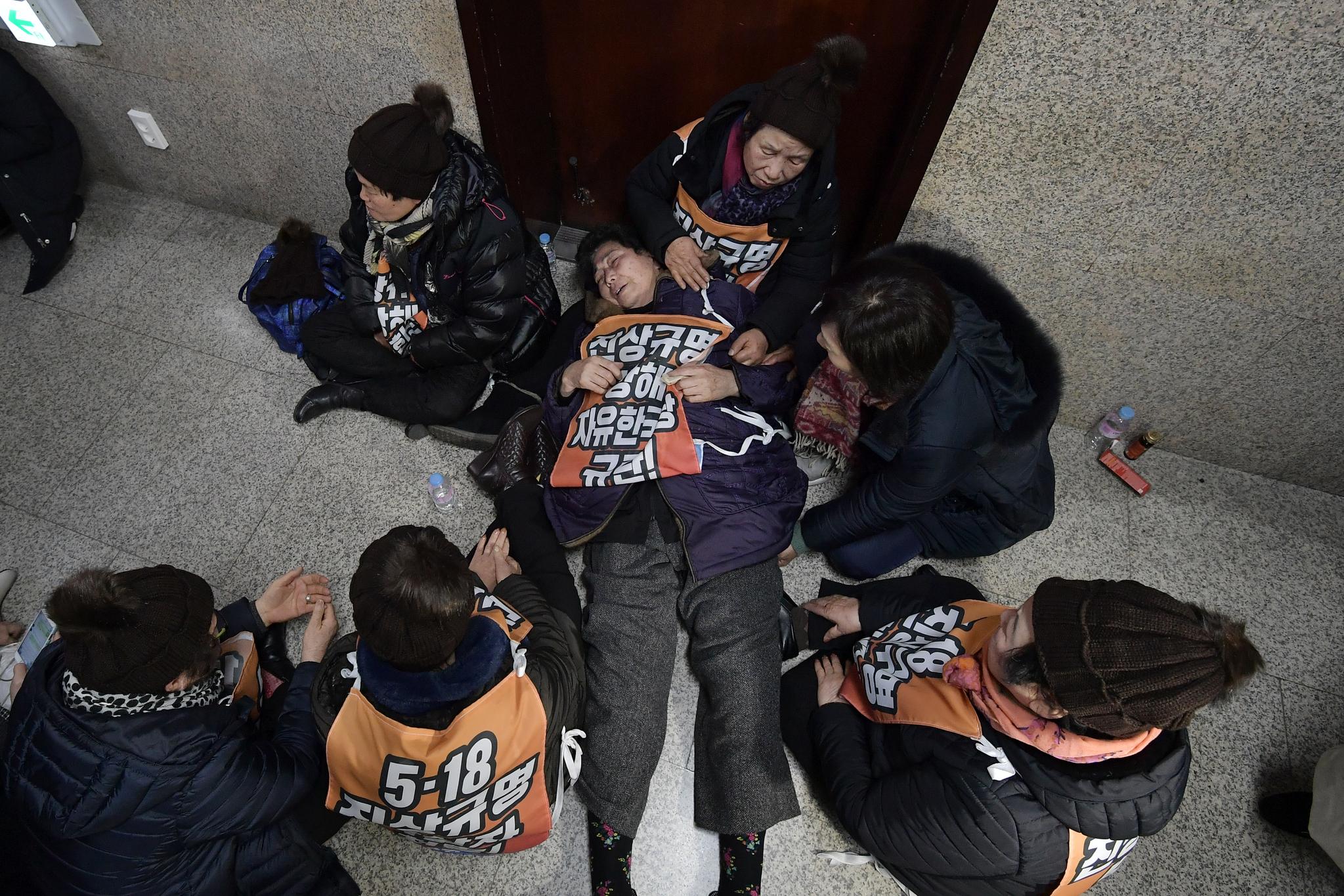 5·18 민주화운동 희생자·부상자 가족들이 14일 국회 자유한국당 원내대표실 앞에서 나경원 원내대표와 5.18 진상규명조사위원 추천 건으로 면담을 요구하며 농성하고 있다. [연합뉴스]
