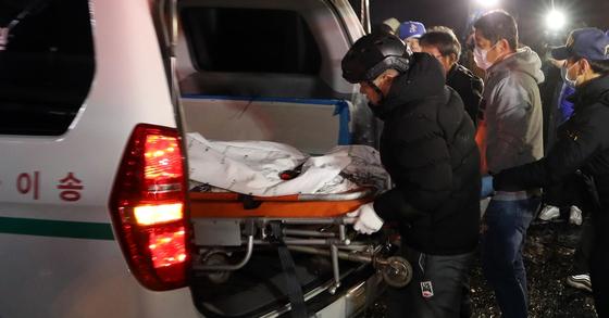 14일 소방대원들이 화재 현장에서 숨진채 발견된 호텔 시설팀장인 김모(51)씨를 구급차량으로 옮기고 있다. [뉴스1]