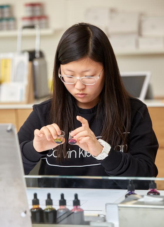 권윤경 학생기자가 유리 비커에 원하는 컬러의 잉크를 조합해 나만의 잉크 컬러를 만들고 있다.