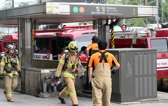 지난 6월 7일 오전 8시 20분께 터널에 연기가 발생해 한때 운행이 지연됐던 2호선 합정역에서 소방관들이 현장 확인 후 승강장에서 나오고 있다. [연합뉴스]