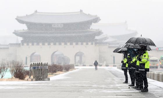 서울을 비롯한 중부지방에 눈이 내린 지난해 12월 16일 오전 서울 광화문광장에서 경찰들이 우산을 쓰고 근무를 하고 있다. [뉴스1]