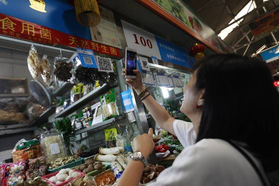 중국 베이징에 있는 한 상점에서 고객이 알리페이로 결제하기 위해 스마트폰을 들어 큐알코드를 찍고 있다. 알리페이를 만든 알리바바의 핀테크 계열사 앤트파이낸셜의 기업가치는 170조원을 돌파했다. [EPA=연합뉴스]