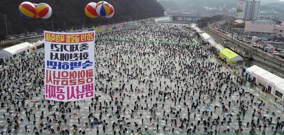 지난 12일 강원도 화천군 산천어축제장에서 얼음벌판을 가득 메운 관광객들이 산천어 얼음낚시를 즐기고 있다. 화천군은 이날 하루 22만 명이 넘는 사람들이 다녀간 것으로 집계했다. [뉴스1]
