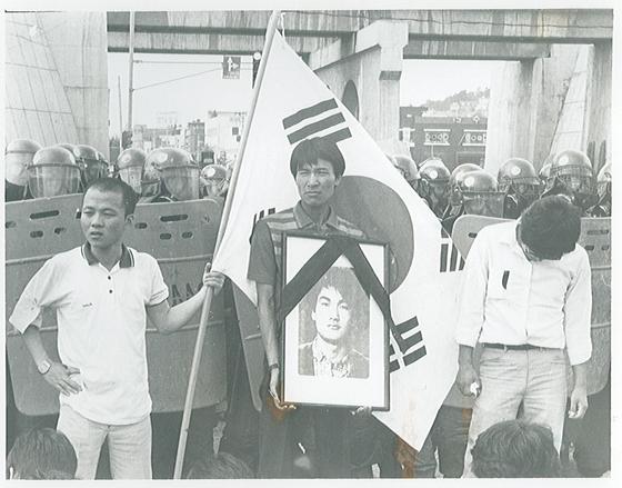 1987년 이한열 열사 장례식 당시 영정 사진을 든 우상호(가운데) 의원. 우 의원 옆에서 태극기를 들고 선 사람은 배우 우현(왼쪽)씨다. [우상호 의원 페이스북]