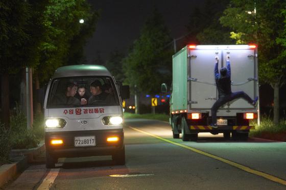 '극한직업' 한 장면. 마약반이 탄 봉고차 오른편 트럭에 매달린 사람이 진선규가 연기한 마 형사다. [사진 CJ엔터테인먼트]