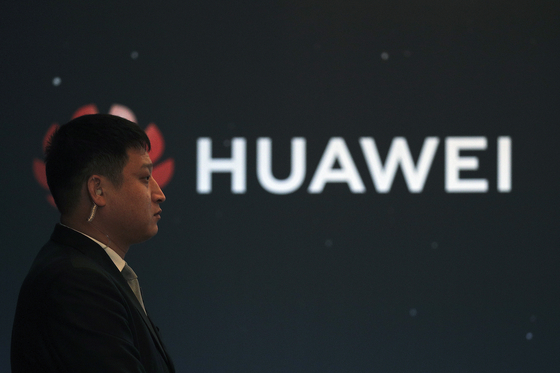 지난 9일 중국 베이징에서 열린 신제품 발표회에서 한 경호원이 화웨이 로고 앞에 서 있다. [AP=연합뉴스]
