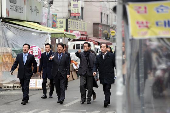 장하성 청와대 정책실장이 18일 일자리 안정자금 홍보 및 소상공인들의 의견을 듣기 위해 서울 관악구 신림사거리 일대 상점가를 방문하고 있는 모습.[사진제공=청와대]