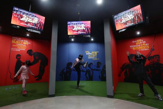 국내에서 스포츠와 기술의 융복합은 시뮬레이션 스포츠에서 가장 활발하게 이뤄지고 있다. 어린이들이 서울월드컵경기장 내 풋볼팬타지움에서 VR 고글을 쓰고 가상 축구 체험을 하고 있다. [사진 올리브 크리에이티브]