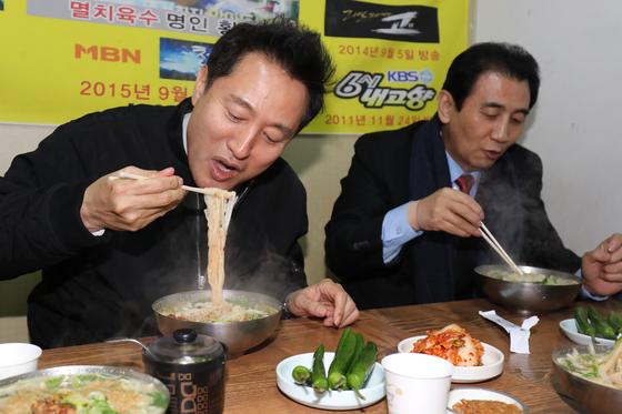 오세훈 전 서울시장이 25일 대구 서문시장을 찾아 칼국수를 맛보고 있다. [뉴스1]