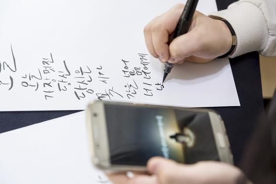 예문을 보고 간단한 문장을 써보고 있는 학생기자들.