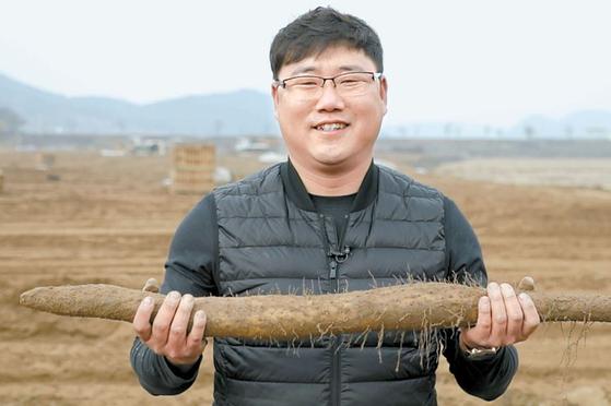 유화성 대표이사는 마·우엉 농사 외길을 걸으며 변화를 통해 농촌의 가치를 혁신해왔다. 마 농장에서 수확한 마를 들어 보이고 있다. [사진 한광호기념사업회]
