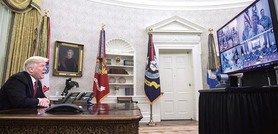 """트럼프 대통령이 성탄절인 지난해 12월 25일(현지시간) 워싱턴DC 백악관 집무실에서 해외 파병 육군·해병대·해군·공군·해안경비대원들과 화상통화를 하고 있다. 트럼프 대통령은 이날 방위비 분담과 관련해 '우리가 불이익을 당하면서 부자 나라들에 보조금 지급하는 걸 원치 않는다""""고 말했다. [연합뉴스]"""