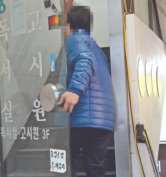 조건부 기초수급자 윤귀선씨가 지난 17일 4년째 살고 있는 서울 이대역 인근 고시원으로 들어가고 있다. 2017년 기초수급자가 된 윤씨의 수입은 생계비·주거비 지원금 월 70만원이 전부다. [최정동 기자]