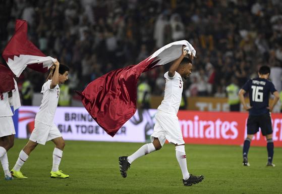 카타르 미드필더 아메드 알리가 아시안컵 우승 직후 자국 국기를 펼쳐보이고 있다. [AP=연합뉴스]