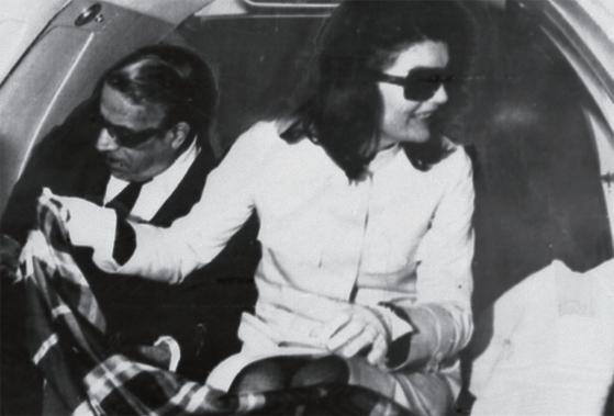 오나시스와 재클린이 비행기 안에서 담요를 무릎에 덮고 있다.