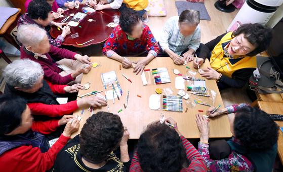 서울 성북구 장위동의 한 경로당에서 강사의 지도를 받으며 노인들이 치매 예방 교육 수업 중 하나인 열쇠고리 만들기를 하고 있다. 강정현 기자