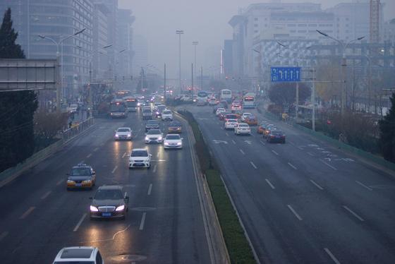 지난해 11월 26일 중국 베이징 시내 거리. 짙은 스모그로 시정거리가 짧아진 탓에 늦은 오후인데도 대부분의 차량이 전조등을 켜고 운행하고 있다. 베이징=강찬수 기자