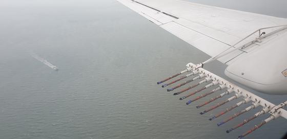 인공강우 실험이 열린 지난 25일 기상항공기가 연소탄 발포를 마치고 이동하고 있다. 바다 위로 기상 선박이 보인다. [기상청 제공]