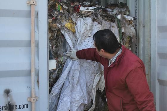지난 3일 필리핀에서 평택항으로 되돌아온 불법 수출 폐기물을 환경부 관계자가 들여다보고 있다. [사진 환경부]