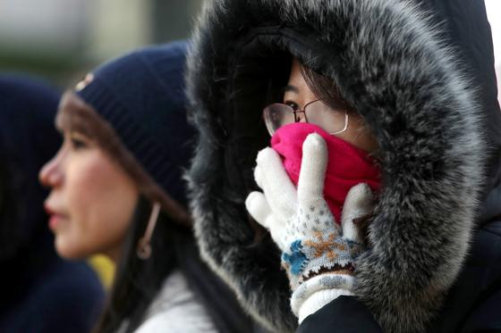 지난 7일 오후 서울 종로구 광화문 네거리 앞에서 한 시민이 옷을 여미고 있다. [뉴시스]