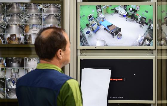 한 병원 관계자가 관제실에서 수술실 CCTV를 점검하고 있다. 전국 병원 중 최초로 CCTV 설치 시범운영을 시작한 이 병원은 수술하는 환자를 대상으로 촬영 동의 여부를 물을 계획이라고 밝혔다. [뉴스1]
