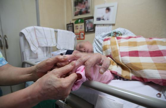 교통사고로 목아래 전신이 마비된 남편을 70세를 넘은 부인이 가사일을 하며 돌보고 있다. 사람이 다치거나 병들고 늙어가는 삶의 모든 과정에서 우리는 돌봄을 받는 수혜자이기도 하고 남을 돌보기도 하면서 살아간다. [중앙포토]