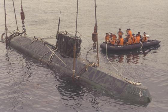 1998년 6월 22일 오후 4시 33분쯤 강원도 속초시 동쪽 해상에서 북한 특수부대 소속 잠수정 1척이 어선의 그물에 걸려 표류하다 해군에 의해 예인됐다. 진해 해군기지로 옮기기 위해 해군 장병이 작업을 하고 있다. [중앙포토]