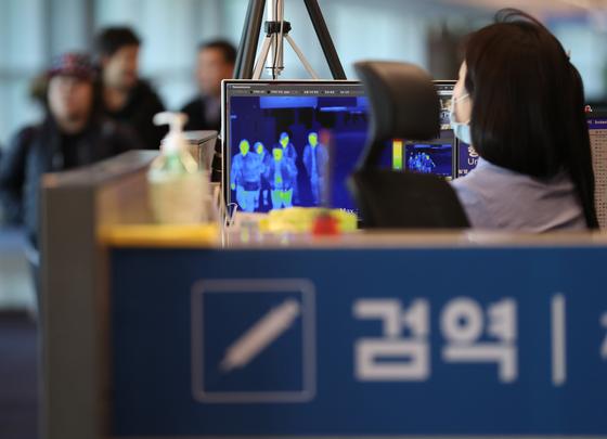 인천공항에서 입국객들이 체온을 측정하기 위한 열화상카메라 앞을 지나고 있다. [연합뉴스]