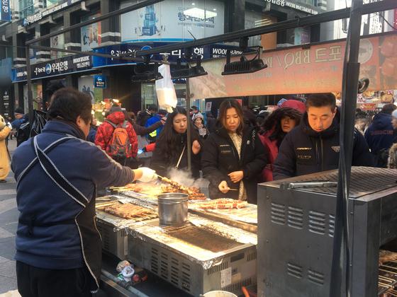서울 명동 거리에서 중국인 관광객이 길거리 음식을 사먹고 있다. 윤상언 기자