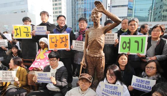 지난해 12월 부산에서 강제징용 피해자를 추모하는 시민단체 회원들이 강제노동자상을 일본 총영사관 앞으로 옮긴 뒤 기념촬영을 하고 있다. 송봉근 기자