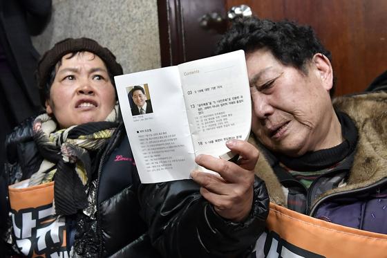 5·18 희생자·부상자 가족들이 지난달 14일 국회 자유한국당 원내대표실 앞에서 극우 논객 지만원씨가 배포한 소책자를 들어 보이며 항의하고 있다. [연합뉴스]