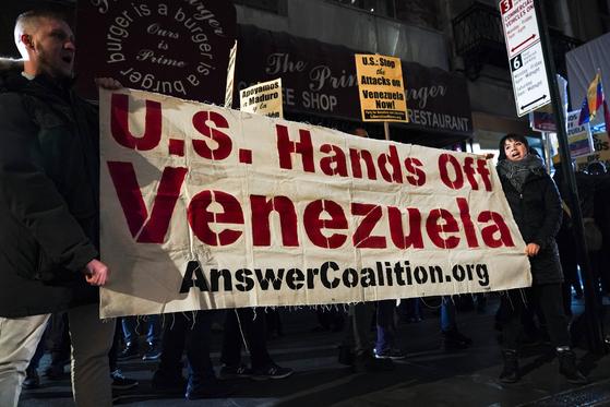 마두로 지지자들이 '미국 정부는 베네수엘라 개입을 중지하라'는 내용의 현수막을 들고 있다. [AFP=연합뉴스]