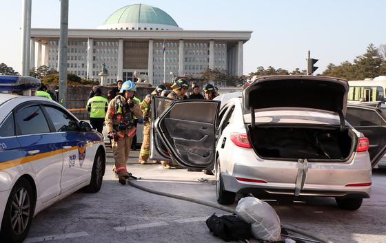 지난 11일 오후 서울 여의도 국회 정문앞에서 한 택시기사가 분신을 시도해 소방관들이 화재진압을 하고 있다. [뉴스1]