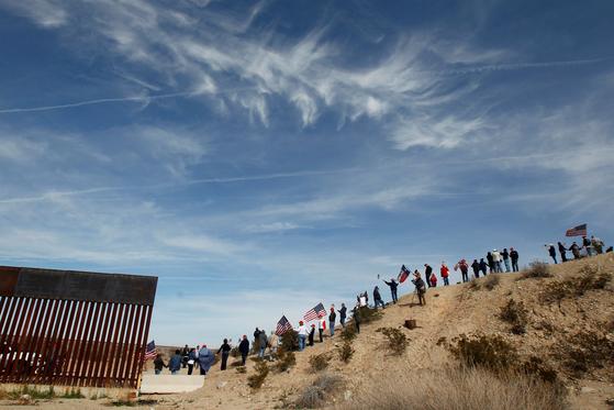 트럼프 지자자들이 지난 9일 미국과 멕시코의 국경이 위치한 뉴멕시코주 선랜드 파크 지역에서 인간장벽을 만들고 있다.[AP=연합뉴스]