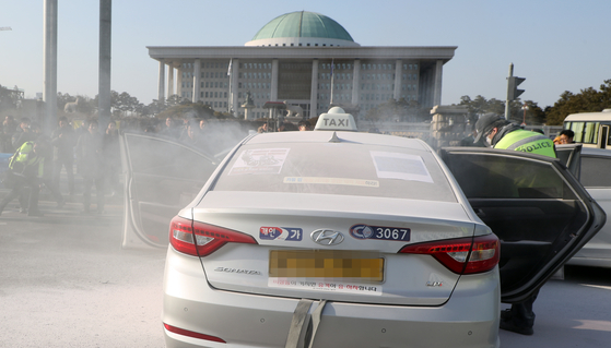 11일 오후 서울 여의도 국회 정문앞에서 한 택시기사가 분신을 시도해 경찰들이 화재진압을 하고 있다. [뉴스1]