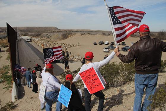 트럼프 지자자들이 지난 9일 미국과 멕시코의 국경이 위치한 뉴멕시코주 선랜드 파크 지역에서 인간장벽을 만들고 있다.이들은 '어린이 인심매매 금지' 등의 문구가 적힌 팻말을 달고 나오기도 했다.[AP=연합뉴스]