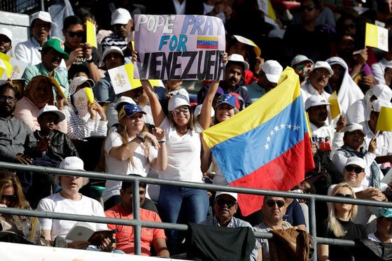 A 프란치스코 교황이 5일 아부다비의 자이드 스포츠 시티 스타디움메서 지전한 미사에서 베네수엘라 출신 이주자들이 국기를 펼치며 자국을 위해 기도해 달라고 요청하고 있다. 베네수엘라는 심각한 경제난에 시달리고 있다. [AP=연합뉴스]